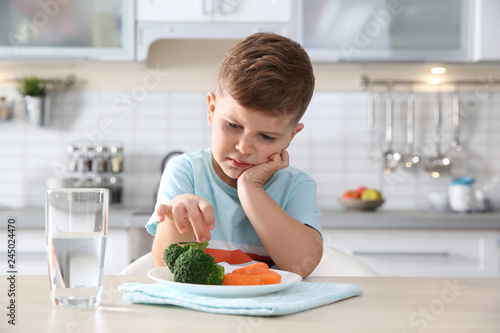 Unhappy little boy eating vegetables at table in kitchen