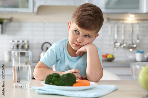 Unhappy little boy with plate of vegetables at table at table