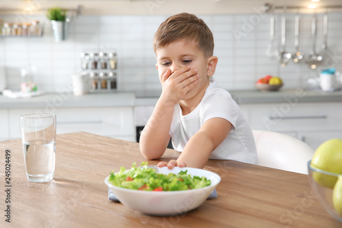 Valokuvatapetti Little boy covering his mouth and refusing to eat vegetable salad at table in ki