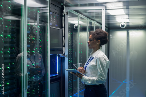 Carta da parati Medium shot of female technician working on a tablet in a data center full of ra