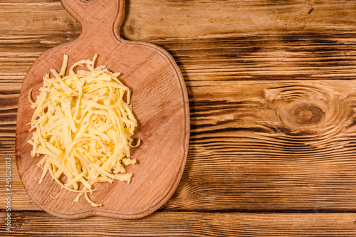 Cutting board with grated cheese on wooden table. Top view