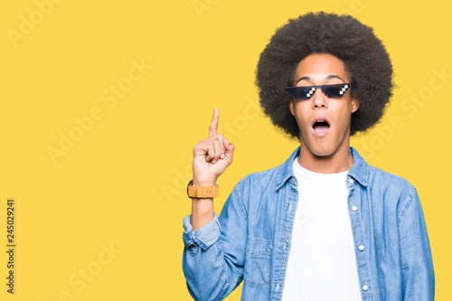 Fotografía  Young african american man with afro hair wearing thug life glasses pointing finger up with successful idea