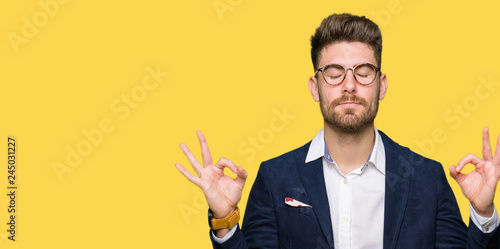 Recess Fitting Zen Young handsome business man wearing glasses relax and smiling with eyes closed doing meditation gesture with fingers. Yoga concept.
