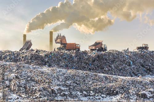 Obraz na plátně  Dump trucks unloading garbage over vast landfill