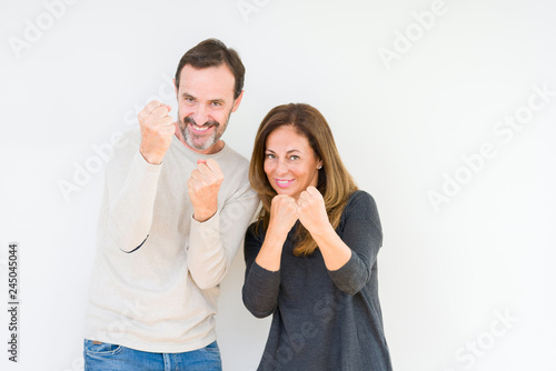 Beautiful middle age couple in love over isolated background Ready to fight with fist defense gesture, angry and upset face, afraid of problem