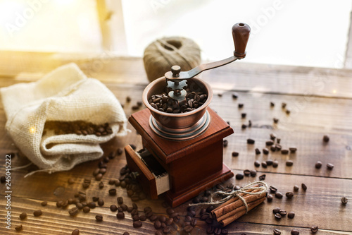 Fotografie, Obraz  Manual coffee grinder on wooden table with sunny window behind