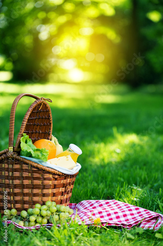 Foto auf Leinwand Picknick Picnic basket with vegetarian food in summer park