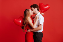 Portrait Of Attractive Young Couple Posing On Red Background And Holding Balloons Heart. Valentine's Day.