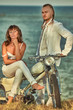 Young romantic couple with vintage custom motorbike on the tropical coast background.