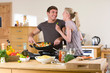 Young couple cooking meal in kitchen at home together