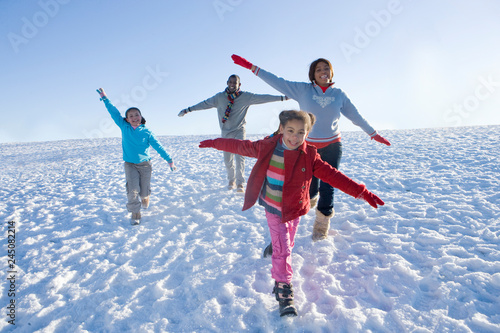 Photo Family on winter vacation running down snowy hill smiling at camera
