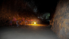 Ghosts Walking Inside Lava River Cave, Bend, Oregon. Long Exposure Photo Of People Passing By Inside A Lava Tube Illuminated By Lantern Light