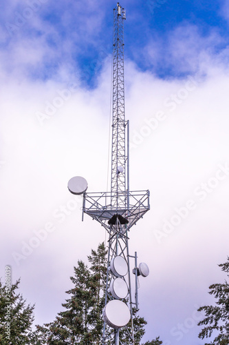 Valokuva  Communication tower with group of parabolic antennas against clouds on a blue sk