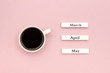 Wooden calendar spring months March April May and Cup of black coffee directed at March on pastel pink paper background. Concept Hello March Creative Top view Flat Lay Greeting card