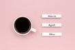 Wooden calendar spring months March April May and Cup of black coffee directed at May on pastel pink paper background. Concept Hello May Creative Top view Flat Lay Greeting card