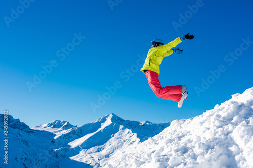 Girl snowboarder jumping and having fun in the winter ski resort.