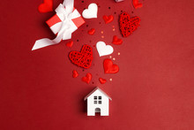 Miniature White Toy House With Hearts And Gifts On Red Background.