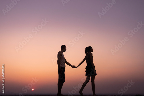 silhouette of couple holding hand and walk at sunset