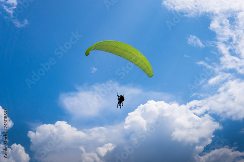 Foto op Canvas Luchtsport Two people are flying on a paraglider in the sky