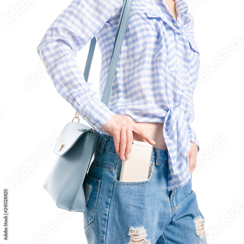 Photo Woman in jeans and blue shirt bag put smartphone pocket in hand macro on white b