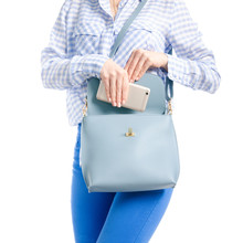 Woman In Jeans And Blue Shirt Put Smartphone In Blue Bag Macro On White Background Isolation