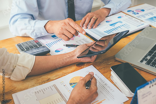 Fotomural Business advisor analyzing financial figures denoting the progress Internal Revenue Service checking document