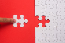 Close Up Of Hand Placing The Last Jigsaw Puzzle Piece On Red Background. Business And Team Work Concept.