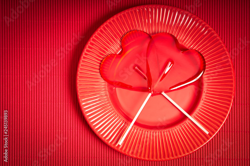 Fotografia  Valentines Day background with red plate and two heart-shaped lollipops on red b