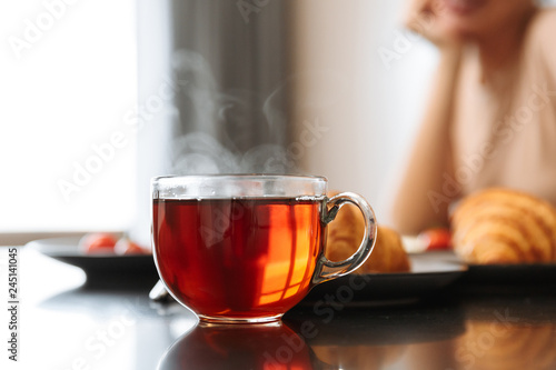 Poster de jardin The Cropped photo of caucasian woman sitting at table in flat, with hot tea in glass