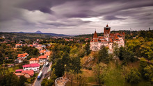 Aerial View Of Bran Castle In Beautiful Transylvania, Region Of Romania Near The Brasov. Cloudy Day With Dark Clouds.