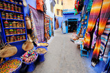 Fototapeta Uliczki - Moroccan handmade crafts, carpets and bags hanging in the narrow street of Essaouira in Morocco with selective focus