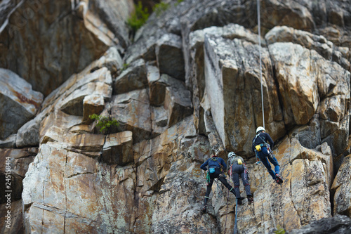 A group of climbers are hanging on a rock wall on a self-insurance Wallpaper Mural