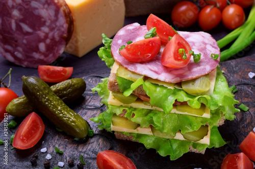 Multi layered club sandwich with rye bread, lettuce salad
