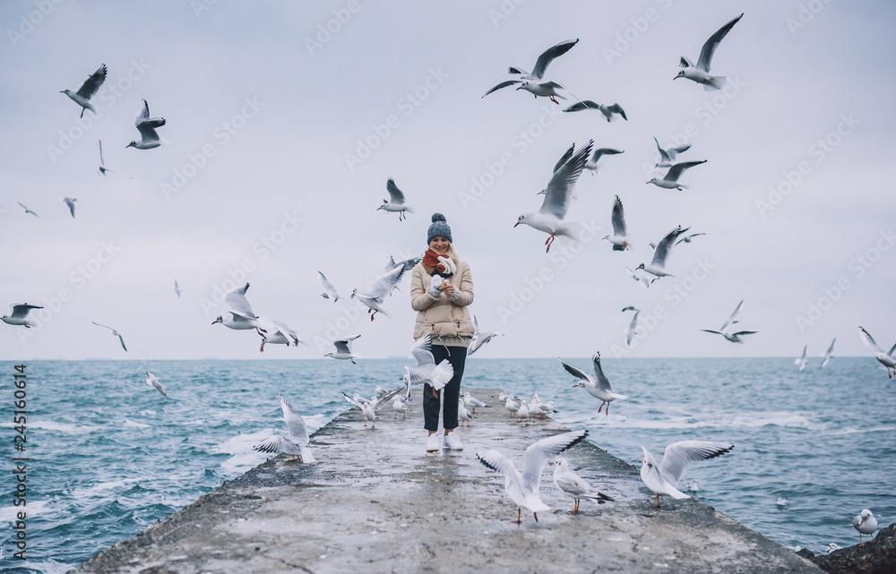 Fotografia Happy young tourist woman feeds seagulls on the sea