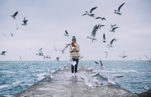 Happy Young Tourist Woman Feeds Seagulls On The Sea. Pretty Female Wearing Coat, Scarf And Watching Flying Seagulls By The Sea In The Sky. People, Travel, Environment, Nature Concept.