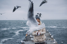 Closeup Portrait Of Young Happy Woman Feeds Seagulls On The Sea. Pretty Female Smiling And Watching Flying Seagulls By The Sea In Front Of Her Face. People, Travel, Environment, Nature Concept.