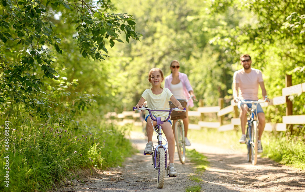 Fototapeta family, leisure and people concept - happy mother, father and little daughter riding bicycles in summer park