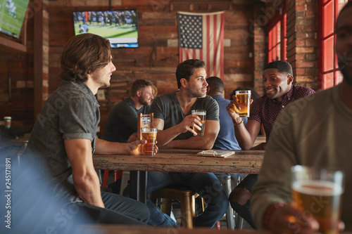 Fototapeta Group Of Male Friends Meeting And Drinking Beer In Sports Bar Together obraz na płótnie