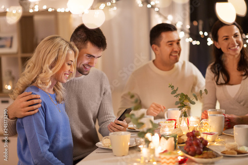 Fototapety, obrazy: celebration, holidays and people concept - happy friends or family with smartphone having tea party at home