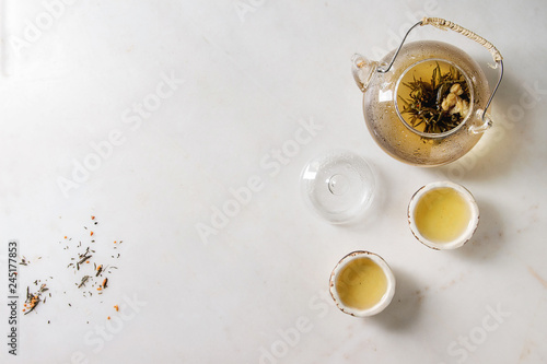 Photo  Hot green tea in two traditional chinese clay ceramic cup and glass teapot over white marble background