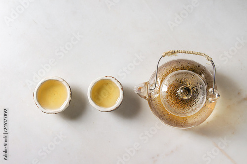 Photo  Hot green tea in two traditional chinese clay ceramic cup and glass teapot in row over white marble background