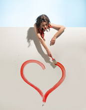 Girl Paints A Heart On The Wall