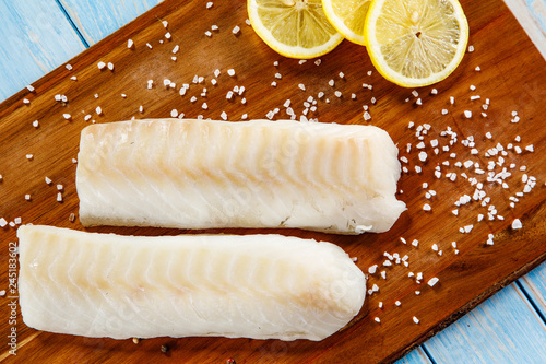 Fresh raw cod served on cutting board on wooden table
