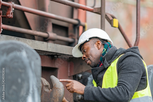 Fotografie, Obraz  African American mechanic wearing safety equipment (helmet and jacket) checking