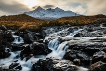 Scenic View Of Waterfall With Snowcapped Mountain In Background