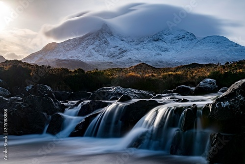 Scenic view of waterfall with snowcapped mountain in background - 245198886