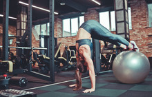 Balance, Strength Concept.Sporty Woman Do Handstand With Legs On Fit Ball. Girl In Sportswear Training On Fitball In Gym. Sport, Fitness Training