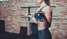 Close-up Of Woman Training With A Skipping Rope In Gym On Brick Wall Background. Cardio Training. Toned Photo.
