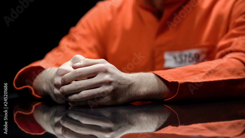 Photo Hand of male prisoner, inmate giving evidence in detention room, cooperation