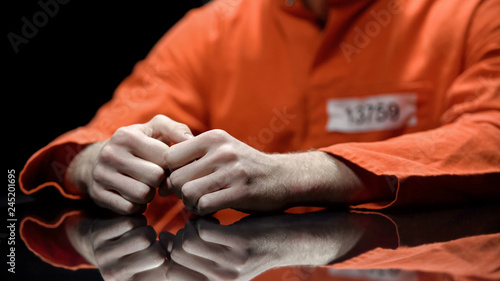 Foto Arrested person hands closeup, prisoner talking to lawyer during interrogation